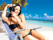 Woman with a camera taking photos on beach Royalty Free Stock Photography