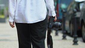 Woman camera walking city street, creative hobby, blogger profession, back view. Stock footage stock footage