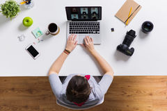 Woman with camera working on laptop at table Stock Photos