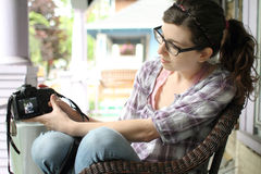 Woman with camera. Young woman showing pictures on a SLR camera Royalty Free Stock Photos