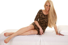 Woman camo nightgown sit on bed legs out Royalty Free Stock Image
