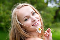 Woman with camomile. Beautiful young woman with camomile, summer day Stock Photo
