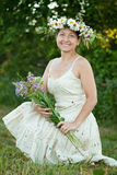 Woman in camomile wreath. Outdoor portrait of mature woman in camomile wreath royalty free stock images