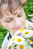 The woman with camomiles. The woman looks at white daisies Stock Image