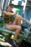 Woman in camouflage shoots from a water pistol Royalty Free Stock Photography