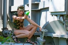 Woman in camouflage shoots from a water pistol Stock Photos