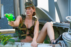 Woman in camouflage shoots from a water pistol Royalty Free Stock Photo