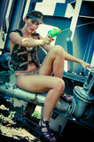 Woman in camouflage shoots from a water pistol Royalty Free Stock Image