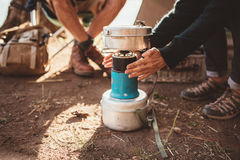 Woman camper warming her hands on camp stove Royalty Free Stock Images