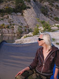 Woman camping. Blonde woman sitting near camping tent Royalty Free Stock Photo