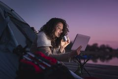 Woman camping by the lake. Young woman camping by the lake, sitting on the tent entrance, drinking hot coffee and reading the news on a tablet computer royalty free stock photos
