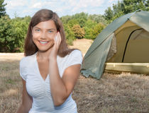 Woman camping mobile phone. Young woman talking on a telephone at campsite with tent in background stock photo