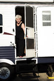 Woman Camping Out. Smiling Woman looking out Trailer Door Stock Photos