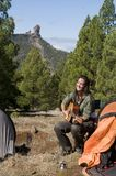 Woman in camping playing guitar Stock Photos