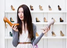 Woman can't choose high heeled shoes Royalty Free Stock Images