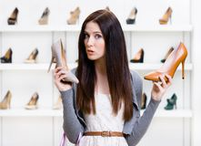 Woman can't choose pumps Stock Images