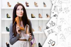 Woman can't choose stylish pumps. Big sales season royalty free stock images