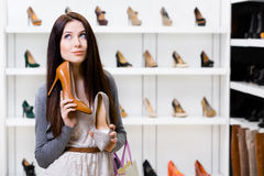Woman can't choose stylish pumps. Woman keeps two stylish pumps in the shopping mall and can't choose the one for her Royalty Free Stock Photography