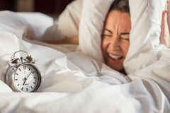 Woman can't listen to that alarm clock Stock Images
