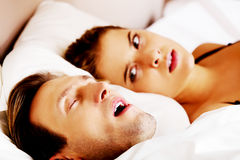 Woman can't sleep becouse her snoring husband.  royalty free stock photos