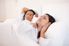 Woman can't sleep next to her snoring boyfriend. Young women can't sleep next to her snoring boyfriend Royalty Free Stock Image