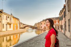 Woman on the canals of ancient village. Environmental portrait of Manopausal woman in red dress walking along the water canals of an old village in Italy Royalty Free Stock Photos