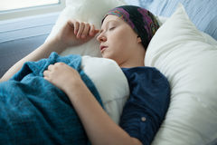 Woman with cancer resting in bed Stock Photos
