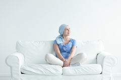 Woman with cancer smiling. Joyously while sitting cross-legged on a couch stock photo