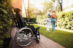 A woman with cancer stands up with her daughter. They embrace. Nearby is a wheelchair woman. A women with cancer stands up with her daughter. They embrace Royalty Free Stock Images