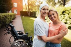 A woman with cancer stands up with her daughter. They embrace. Nearby is a wheelchair woman. A women with cancer stands up with her daughter. They embrace Royalty Free Stock Photo