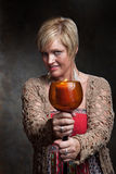 Woman With Candle. Caucasian woman holds candle with wily smile Stock Images