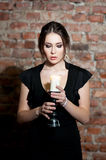 Woman with candle in black dress on brick wall bac Royalty Free Stock Images