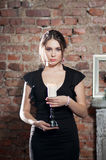 Woman with candle in black dress on brick wall bac Stock Image
