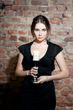 Woman with candle in black dress on brick wall bac Royalty Free Stock Photo