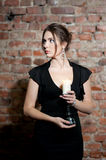 Woman with candle in black dress on brick wall background. Elegance. Silence Stock Photography