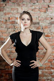 Woman with candle in black dress on brick wall background. Elegance. Silence Stock Photos