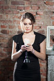 Woman with candle in black dress on brick wall background. Elegance. Silence Royalty Free Stock Photo