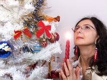 Woman with candle near Christmas tree Stock Images