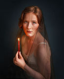 Woman with candle under black veil. Halloween photo Stock Photo