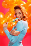 Woman with candy. Portrait of happy young woman biting candy over balloons Stock Photos