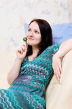 Woman with candy on the sofa Stock Image