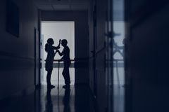 Doctor and patient with stick are standing in hallway. Woman with cane is visiting hospital. Attentive therapist is meeting her in corridor and supporting by stock photos