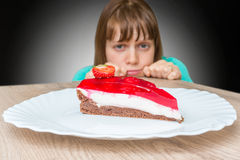 Woman cannot resist the temptation and wants to eat sweet cake Stock Photos