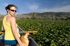 Woman in a canoe with her dog Stock Photography