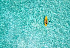 Woman in a canoe over turquoise, tropical waters. In the Maldives stock photo
