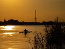 Woman canoeing at sunset on Vistula river, Poland. Amazing scenery and colors. Woman canoeing at sunset on Vistula river, Poland. Amazing scenery stock photos