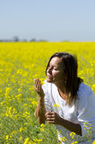 Woman in Canola Field. A beautiful mature woman in a blossoming field of canola enjoying the scent of the flowers stock images