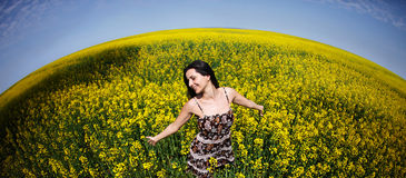 Woman in canola world. Happy girl playing in a yellow world of canola stock image
