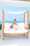 Woman on canopied seat with laptop. Fresh bright portrait of a woman sitting cross legged on a canopied seat with her laptop backed by a large window overlooking Royalty Free Stock Photo