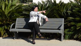 Woman cant stop laughing on the bench. Mature woman cant stop laughing on the park bench when sees something funny stock video footage